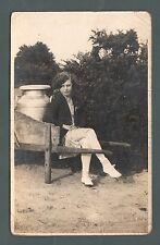 ,Young lady with milk-churn on wheelbarrow, smart clothes, wavy hair, RP,  qb878