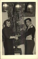Christmas - Young Couple Poses In Front of Tree Amateur Real Photo Postcard