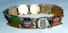 A VINTAGE BRASS SOUVENIR OF PARIS TRAVEL BRACELET WITH COLOURED ENAMEL PANELS