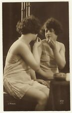 PRETTY WOMAN WEARING NEGLIGEE APPLIES LIPSTICK IN FRONT OF A MIRROR  (J MANDEL)