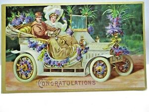 1910 POSTCARD CONGRATULATIONS, COUPLE IN EARLY CAR WITH PURPLE FLOWERS
