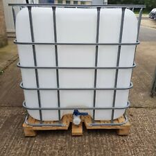 IBC 1000 litre storage container tank in a metal cage fixed to a wooden pallet.