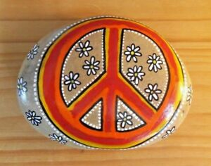 Hand painted rocks, stones, pebbles. Peace sign with flowers on a pebble.