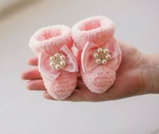 Handmade knitted pink baby shoes with with decorative brooch for newborns