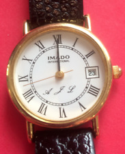 LADIES 'IMADO' WATCH GOLD COLOUR CASE, WHITE DIAL. BLACK STRAP, INITIALLED 'AJL'