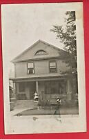 RPPC HOUSE WITH GIRL ON PORCH  BOY HOLDING DOG IN YARD ALBION MICH ?