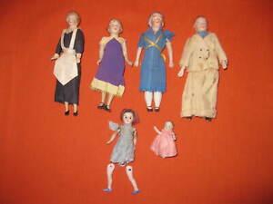 6 PORCELAIN ?GERMAN? MOLDED DOLLS: 1 MAN, 3 LADIES. 1 BABY, 1 CHILD (RESTRING 1)