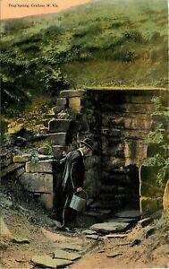 1913 WEST VIRGINIA POSTCARD: MAN FILLING BUCKET AT TRAP SPRING, GRAFTON, W. VA.