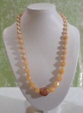 NECKLACE WITH PEACH / TAN BEADS AND A GOLD CENTER BEAD