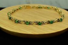 "7"" 10K YELLOW GOLD GREEN EMERALD TENNIS BRACELET WITH DIAMOND ACCENTS"