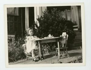 Little girl having tea party with her toy doll -  Vintage snapshot photo