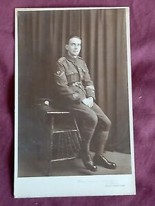 VINTAGE WW 1 ERA REAL PHOTO POSTCARD, YOUNG SOLDIER IN UNIFORM AT A PHOTO STUDIO