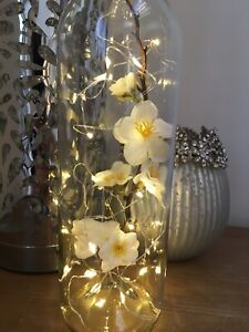 Wine bottle with lights and white cherry blossom