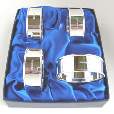 FOUR SILVER NAPKIN RINGS.  A BOXED SET OF 4 EDINBURGH HALLMARKED SERVIETTE RINGS