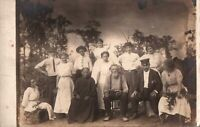 VINTAGE POSTCARD GROUP OF PEOPLE IN STAGED PHOTO ON RPPC SOME RUST ON REAR