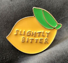 Slightly Bitter - With Gold Lettering And Outlined Lemon shaped enamel pin badge