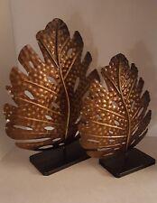 2 extra large metal distressed leaves on black pedestals