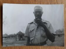 1946 B/W Photograph. African Man in Uniform, Smoking. Hut Background. Gambia