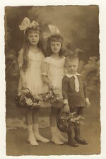 PORTRAIT OF THREE ADORABLE SIBLINGS (GERMAN REAL PHOTO POSTCARD 1920'S)