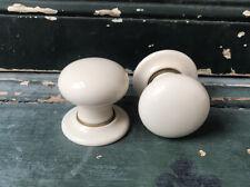 A pair of cream porcelain & brass door handles,