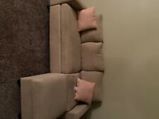 Main Stays Tan couch with pink pillows