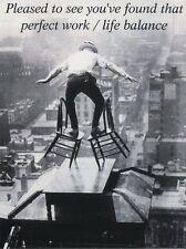 POST CARD OF OLD PHOTOGRAPH OF MAN BALANCING HIGH ABOVE THE GROUND IN A CITY