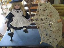 Jolie poupée en porcelaine accompagnée d'un banc en fer forgé et d'un parasol