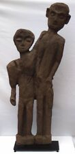 4 foot high primitive and stylized carving of two people on custom metal base.