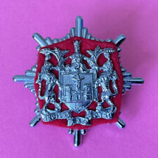 More details for an old  wigan  fire brigade, cap badge.