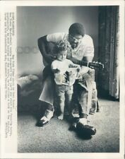 1973 Press Photo Rosey Grier Looks at Needlepoint With His Young Son