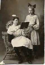 Sisters Try to Look Natural Reading Book. Bows in hair Cropped Cabinet photo