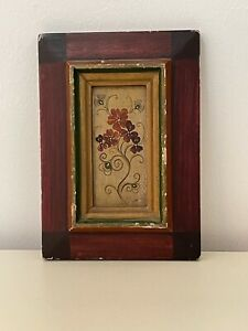 An antique wooden frame with a red rose on it