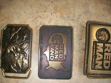 Three vintage brass belt buckles. Two Red Man and one Mallard