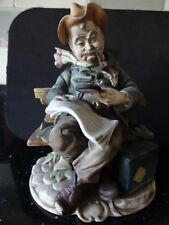 BOND WARE BISQUE FIGURINE OF AN OLD MAN READING WITH A MAGNIFYING GLASS.