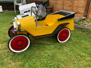 A Classic Ride-in Child's Pedal Car In Yellow With Chrome Grille. Hardly Used.