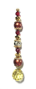 Handmade green & red bead suncatcher w/ gold & clear bead accents. Copper hook.