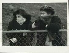 New listing 1986 Press Photo A pair of girls bundled up for cold weather stand behind fence