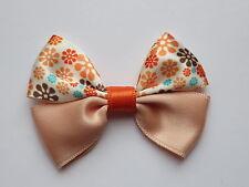 Petit noeud papillon cheveux saumon et fleurs sur barrette élastique pince